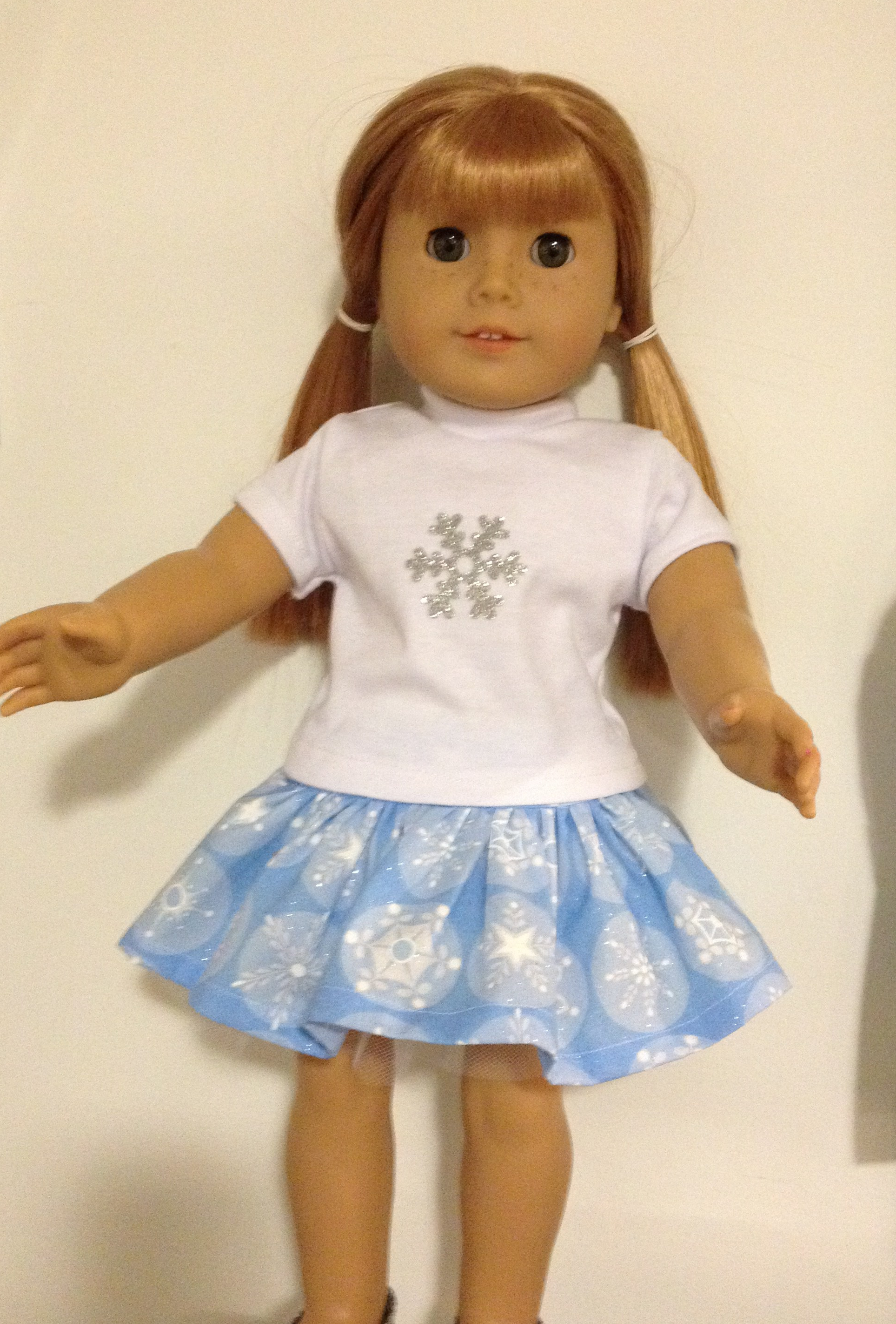 Make a sparkly snowflake tee shirt for your 18 inch doll with this quick and easy HTV tutorial by Oh Sew Kat! Find more sewing patterns for American Girl dolls (free skirt pattern) at www.ohsewkat.com. #ohsewkat #cricuttutorial #dollteeshirt #htvtutorial #dollcraft