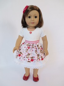 American Girl doll in white dress with Valentine apron and heart button