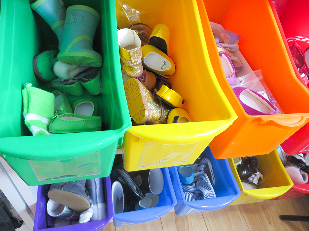 Organize your 18 inch doll's shoe collection in just 15 minutes. For less than $10 you can buy a set of book boxes and sort the shoes in rainbow order. It's pretty and functional and makes clean up easy! #dollshoes #organization